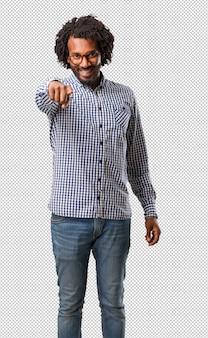 Homem afro-americano de negócios bonito alegre e sorridente apontando para a frente