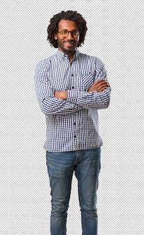 Homem afro-americano de negócios bonito cruzando os braços, sorridente e feliz, sendo confiante e amigável