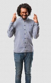 Homem afro-americano de negócios bonito cruzando os dedos