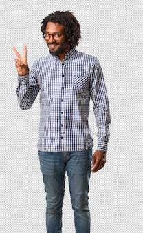 Homem afro-americano de negócios bonito divertido e feliz, positivo e natural, faz um gesto de vitória, o conceito de paz