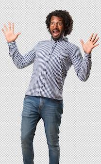 Homem afro-americano de negócios bonito gritando feliz, surpreso por uma oferta ou promoção, escancarado, pulando e orgulhoso