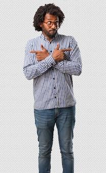 Homem afro-americano de negócios bonito homem confuso e duvidoso, decidir entre duas opções, conceito de indecisão