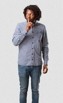 Homem afro-americano de negócios bonito mantendo um segredo ou pedindo silêncio, rosto sério, conceito de obediência