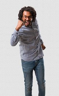 Homem afro-americano de negócios bonito muito feliz e animado, levantando os braços
