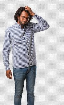 Homem afro-americano de negócios bonito preocupado e oprimido, esquecido, perceber algo, expressão de choque por ter cometido um erro