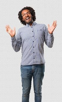 Homem afro-americano de negócios bonito rindo e se divertindo, sendo relaxado e alegre, sente-se confiante e bem sucedido