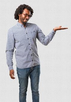 Homem afro-americano de negócios bonito segurando algo com as mãos, mostrando um produto, sorridente e alegre, oferecendo um objeto imaginário