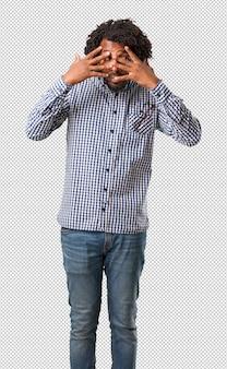 Homem afro-americano de negócios bonito sente-se preocupado e com medo, olhando e cobrindo o rosto