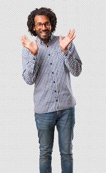 Homem afro-americano de negócios bonito surpreso e chocado
