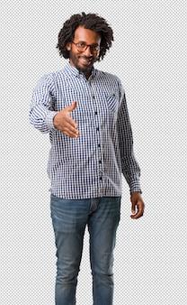 Homem afro-americano do negócio considerável que alcança para fora para cumprimentar alguém ou gesticular para ajudar