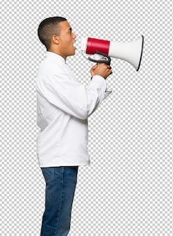 Homem afro americano jovem chef gritando através de um megafone para anunciar algo em posição lateral