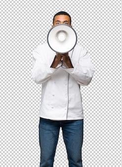 Homem afro-americano jovem chef gritando através de um megafone para anunciar algo