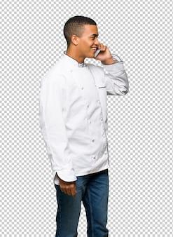 Homem afro-americano jovem chef, mantendo uma conversa com o telefone móvel