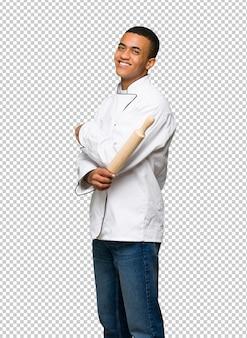Homem afro americano jovem chef olhando por cima do ombro com um sorriso