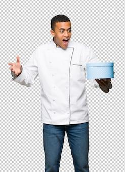 Homem afro-americano jovem chef segurando a caixa de presente nas mãos