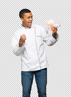 Homem afro-americano jovem chef tomando um monte de dinheiro