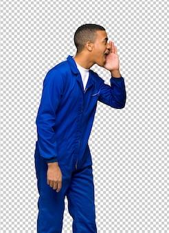 Homem afro-americano jovem trabalhador gritando com a boca aberta para o lateral