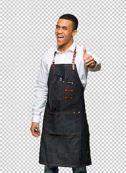 Homem afro-americano novo do barbeiro que dá os polegares acima do gesto porque algo bom aconteceu