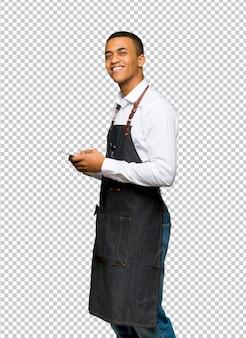 Homem afro-americano novo do barbeiro que envia uma mensagem com o móbil