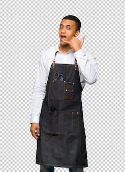 Homem afro-americano novo do barbeiro que faz o gesto do telefone. me ligue de volta