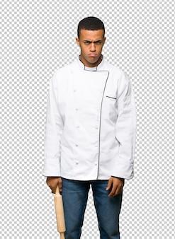 Homem afro-americano novo do cozinheiro chefe com expressão triste e deprimida