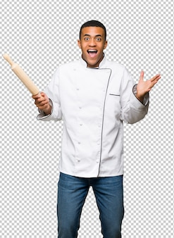 Homem afro-americano novo do cozinheiro chefe com surpresa e expressão facial chocada