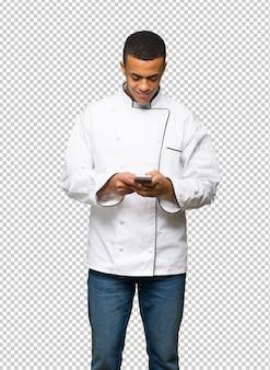 Homem afro-americano novo do cozinheiro chefe que envia uma mensagem com o móbil