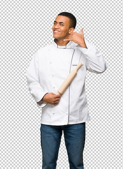Homem afro-americano novo do cozinheiro chefe que faz o gesto do telefone. me ligue de volta