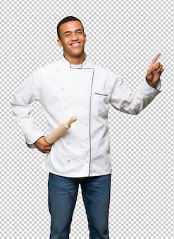 Homem afro-americano novo do cozinheiro chefe que mostra e que levanta um dedo no sinal do melhor