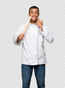 Homem afro-americano novo do cozinheiro chefe que sorri com uma expressão feliz e agradável