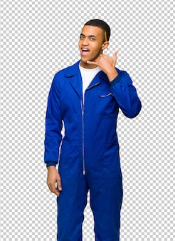 Homem afro-americano novo do trabalhador que faz o gesto do telefone. me ligue de volta