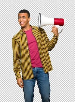 Homem afro-americano novo que toma um megafone que faça muito ruído