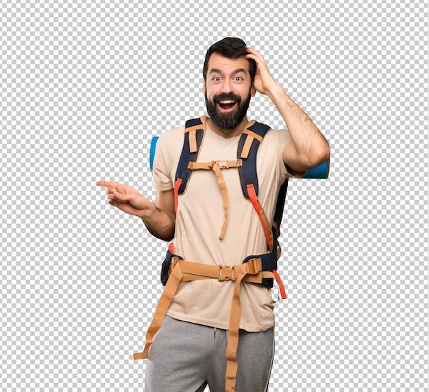 Homem alpinista surpreso e apontando o dedo para o lado