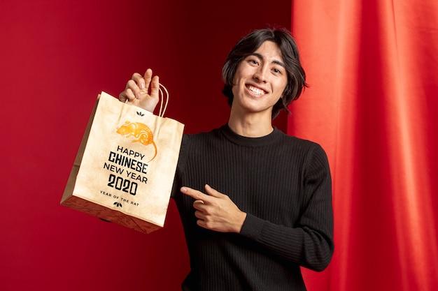 Homem apontando para bolsa com mensagem de feliz ano novo
