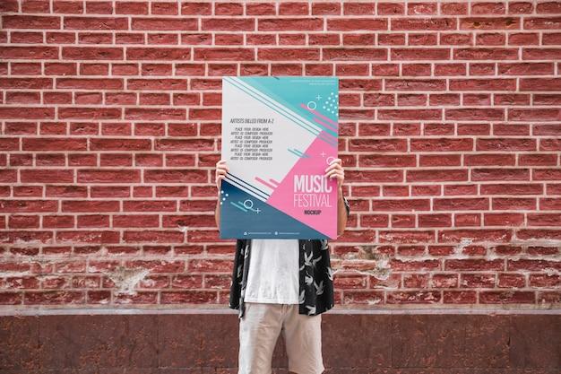 Homem, apresentando, cartaz, mockup, frente, parede tijolo