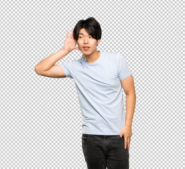 Homem asiático com camisa azul, ouvindo algo, colocando a mão sobre a orelha