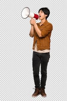 Homem asiático com casaco marrom gritando através de um megafone