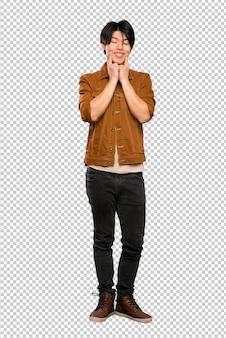 Homem asiático com casaco marrom sorrindo com uma expressão feliz e agradável