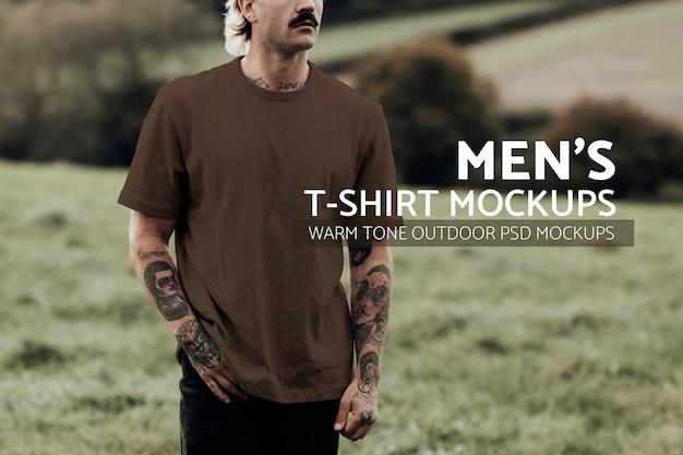 Homem atraente em uma camiseta marrom com espaço de design em pé no campo