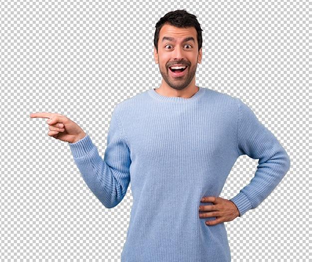 Homem bonito, apontando o dedo para o lado e apresentando um produto