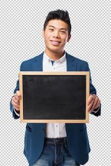 Homem bonito chinês segurando um quadro-negro