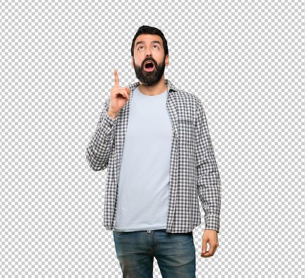 Homem bonito com barba apontando para cima e surpreso