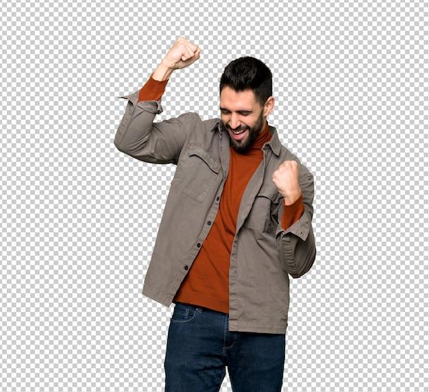 Homem bonito, com barba, celebrando uma vitória