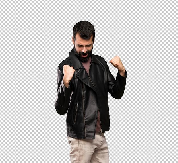 Homem bonito com barba comemorando uma vitória na posição de vencedor