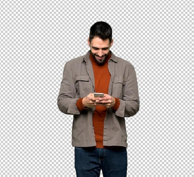 Homem bonito com barba enviando uma mensagem com o celular