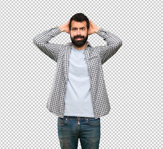 Homem bonito com barba frustrada e leva as mãos na cabeça