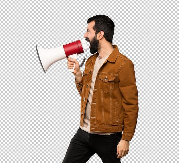 Homem bonito com barba gritando através de um megafone