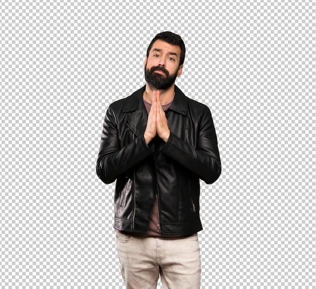 Homem bonito com barba mantém a palma da mão juntos. pessoa pede algo