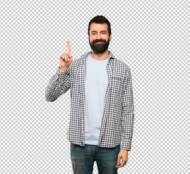 Homem bonito com barba mostrando e levantando um dedo em sinal dos melhores