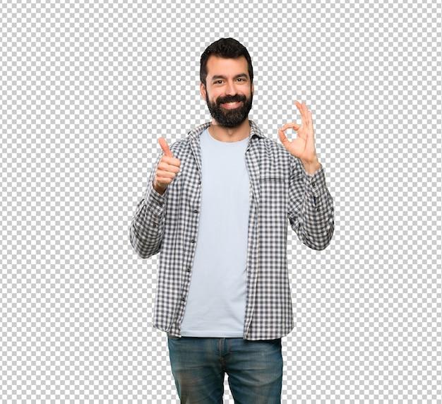 Homem bonito com barba mostrando sinal de ok e o polegar para cima gesto